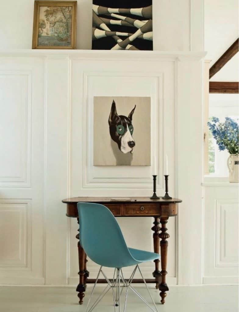 An Antique Kidney Desk and Blue Eames Chair In A Modern Room